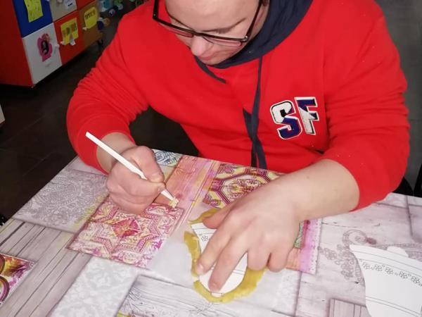 Un ragazzo disabile colora dei lavoretti natalizi al centro Starbene di Bari